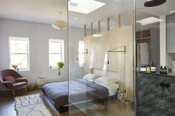 """The top floor bedroom is designed with the concept of """"objects defying space,"""" where the headboard is also a closet wall and a glass shower cube creates an en suite bath. The pendant light is a Noguchi A Akari Lamp. In the corner is an Eero Saarinen Womb Chair and aDoug Johnston basket."""