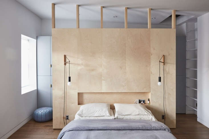 The headboard, made of birch ply millwork by Hub Woodworks, is open at the top to allow light into the built-in closet behind. The lights are Andrew Neyer Crane Wall Lights.