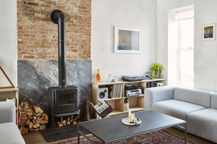 A slab of Palissandro Blue marble is used for fireplace cladding behind the Morsø 3440 Stove. The sofas are Hay Mags
