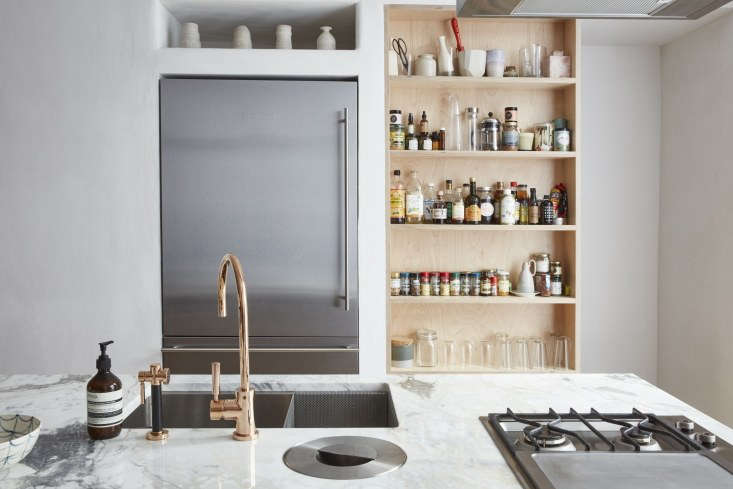 A Liebherr 30-Inch Built-In Refrigerator is flanked with a bank of plywood shelving with a clear coat. The kitchen island has a Bosch 800-Series Dishwasher, aBertazzoni Electric Wall Oven, and aBertazzoni Gas Cooktop. The sink is a Kraus 36-inch stainless steel basin and the faucet is a Dornbracht Tarain rose gold from the Cyprum line. Inset into the marble top is an in-counter compost bin.