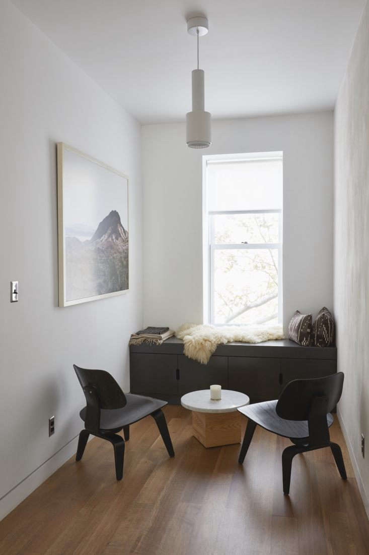 An open alcove on the second floor is one of two spaces framing the staircase that was opened up to bring light and cross ventilation to the floor. The reading nook, complete with black built-in storage shelves, has two Eames Molded Plywood Lounge Chairs in ebony and a Carrara marble table handmade by Keith.