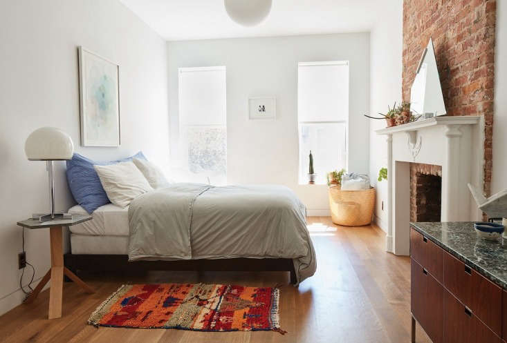 The second-floor guest room is furnished with a vintage Florence Knoll rosewood credenza, Fort Standard Elevate Table, vintage lamp, and rug. On the bed is a long body pillow from The Primary Essentials own line (contact TPE for info).