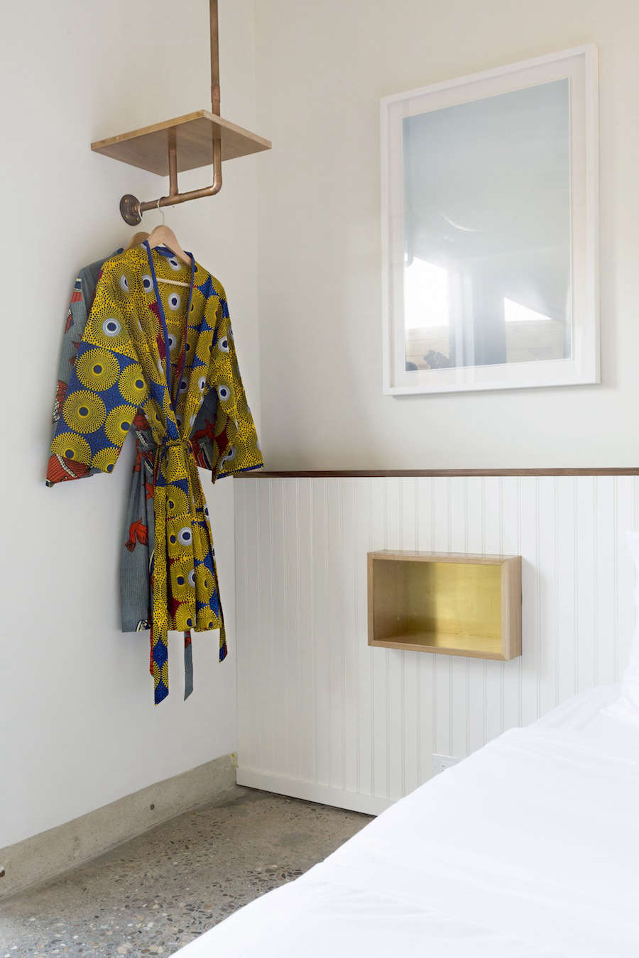 Custom robes are made from deadstock African fabrics. The side-table nooks and shelving are hand-made from American white oak with brass details.