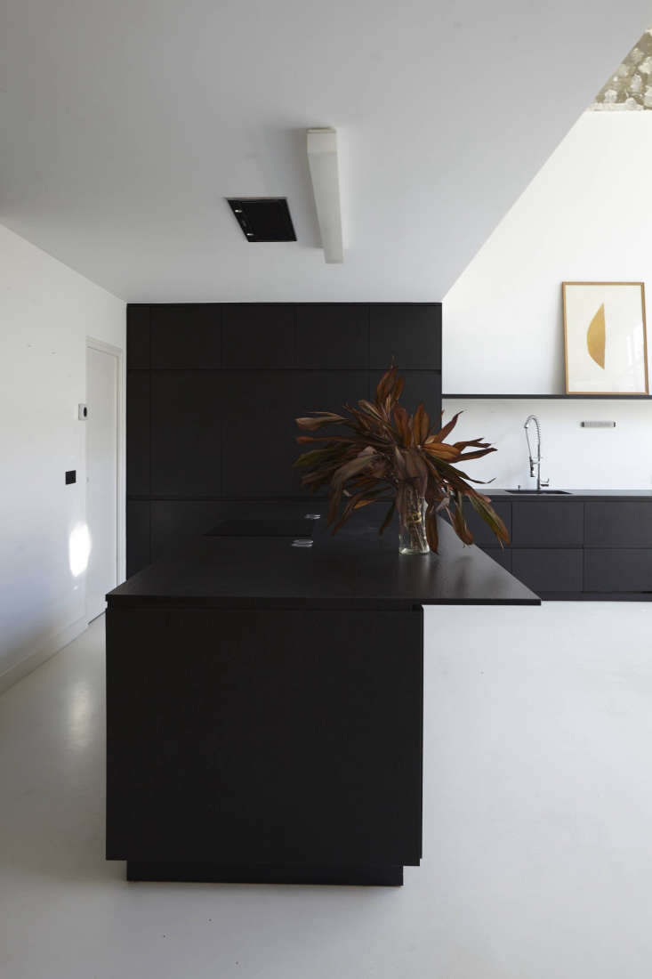 Sisto designed the kitchen custom for the space. It's made of black wood and Zimbabwe black granite cabinet fronts and countertops (from Marbrerie Boucon).