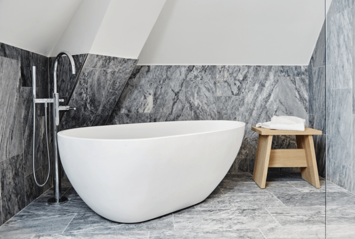 A guest bath feels elegant despite its pared-down elements: a sculptural bath paired with a floor-mounted faucet and simple wooden stool.