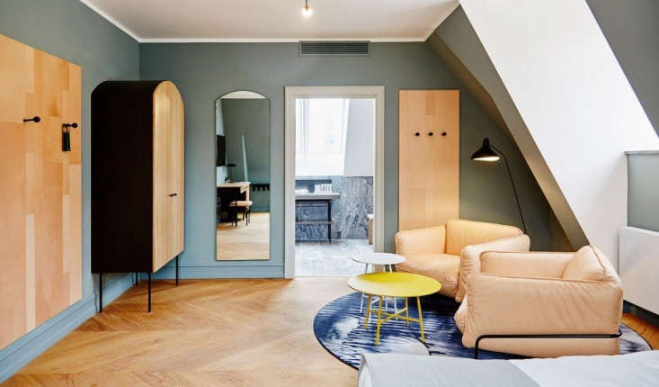 In the hotel, the traditional guest rooms provide a backdrop for furniture by Danish company Carl Hansen & Søn; unexpected shapes and wall-mounted boards add an artful, almost sculptural note. (Note the chevron-patterned floors.)