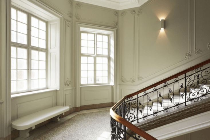 For a minimalist-meets-maximalist interior, let ornate details stand on their own. The architects preserved many of the original architectural details, including a wood and marble staircase, and added little in the way of furniture and lighting to give it a grand but stripped-down look.