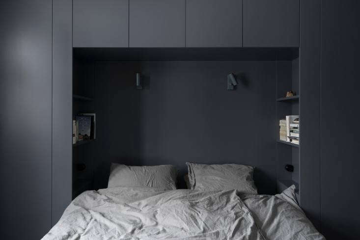 A built-out wall of cabinets creates a nook for a bed—and hidden shelves within reach. See A Darkly Romantic House in Sweden by Skälsö Architects for more.