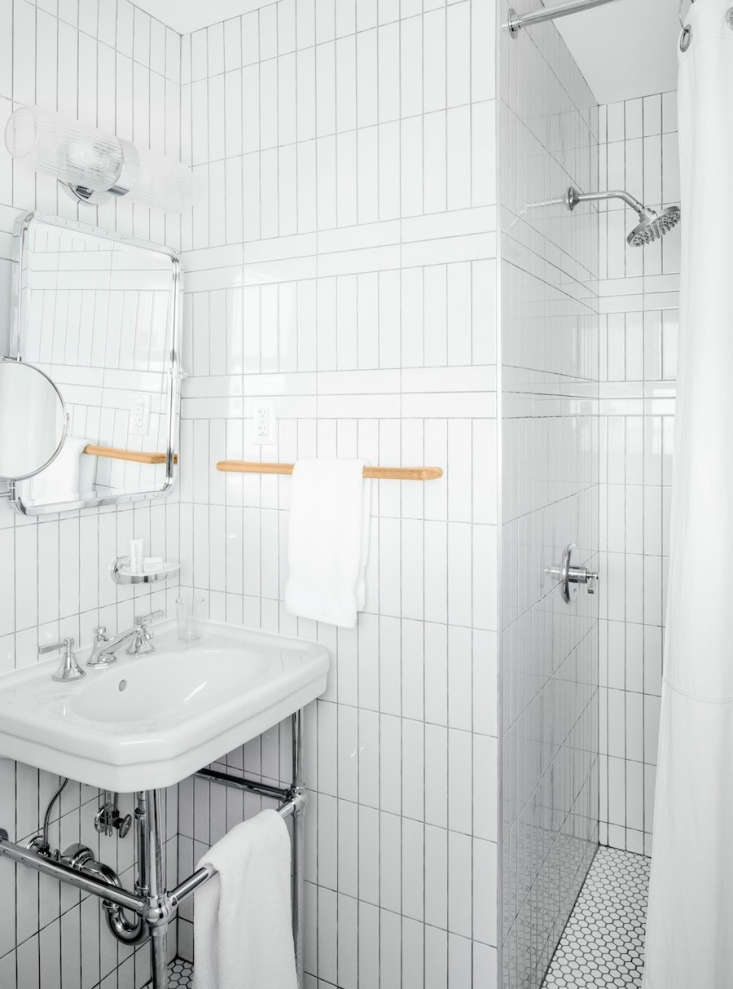 the guest bathroom has floor to ceiling white ceramic tilelaid vertically and 19
