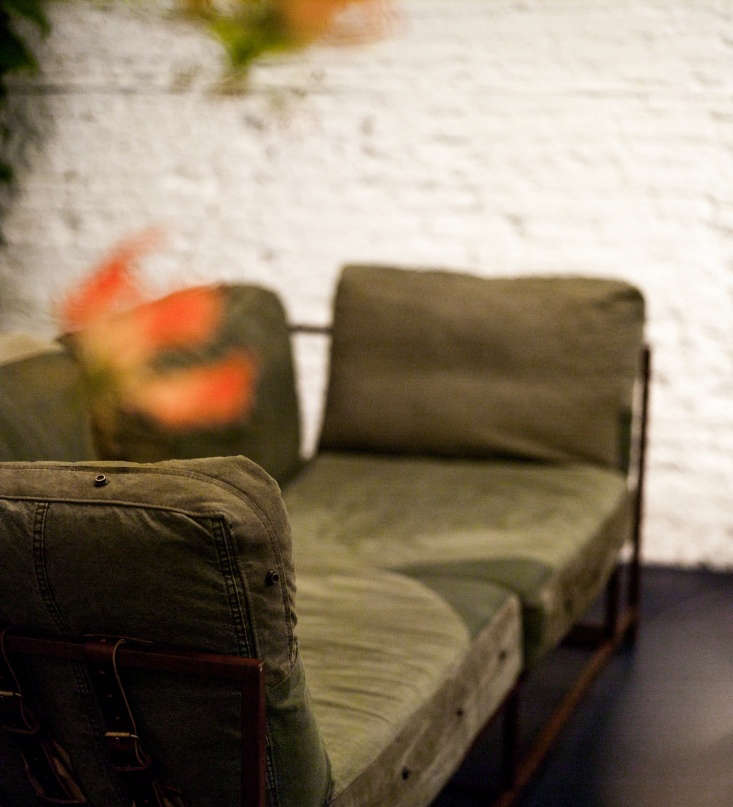 a two seat couch upholstered in vintage olive green military canvas with leat 14