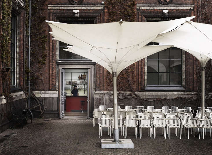 The courtyard leading into Apollo & Bar and Kantine at Kunsthal Charlottenborg. The chairs are the HAY Palissade Outdoor Armchair in white.