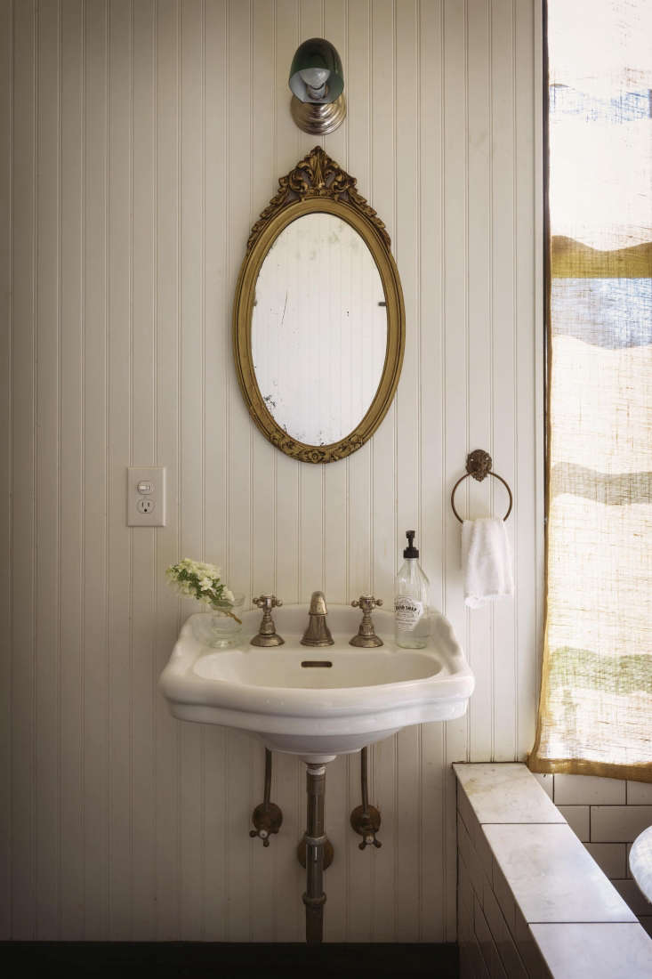 The sink is from Signature Hardware and the green-glass-shaded sconce is from Y Lighting.