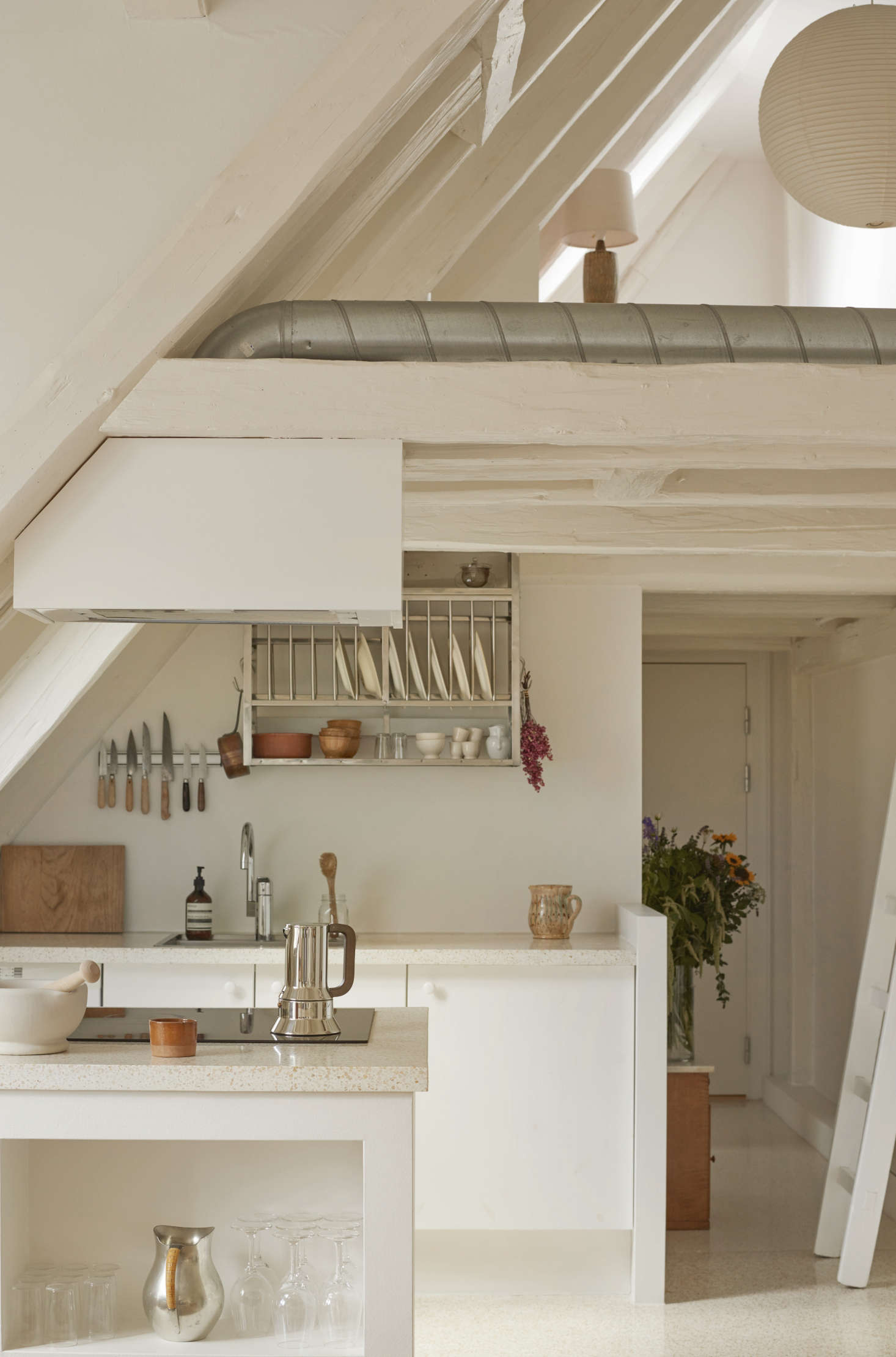 The all-white kitchen sits beneath a lofted home office on the top floor of the historic building. Photograph courtesy of Katrine Rohrberg from Danish Heritage: A Copenhagen Townhouse Renovated by Hand.