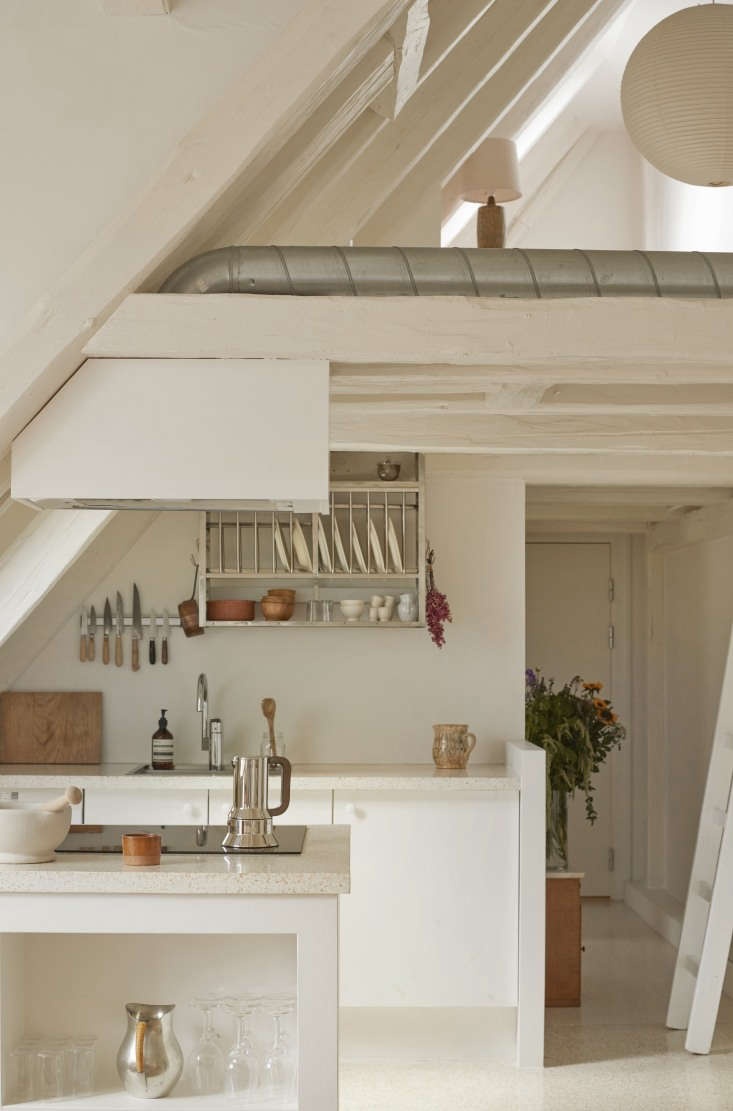 The all-white kitchen sits beneath a lofted home office on the top floor of the historic building. Photograph courtesy ofKatrine RohrbergfromDanish Heritage: A Copenhagen Townhouse Renovated by Hand.