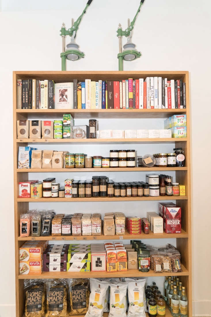 Cookbooks, herbs, and dried goods are organized neatly on shelves.