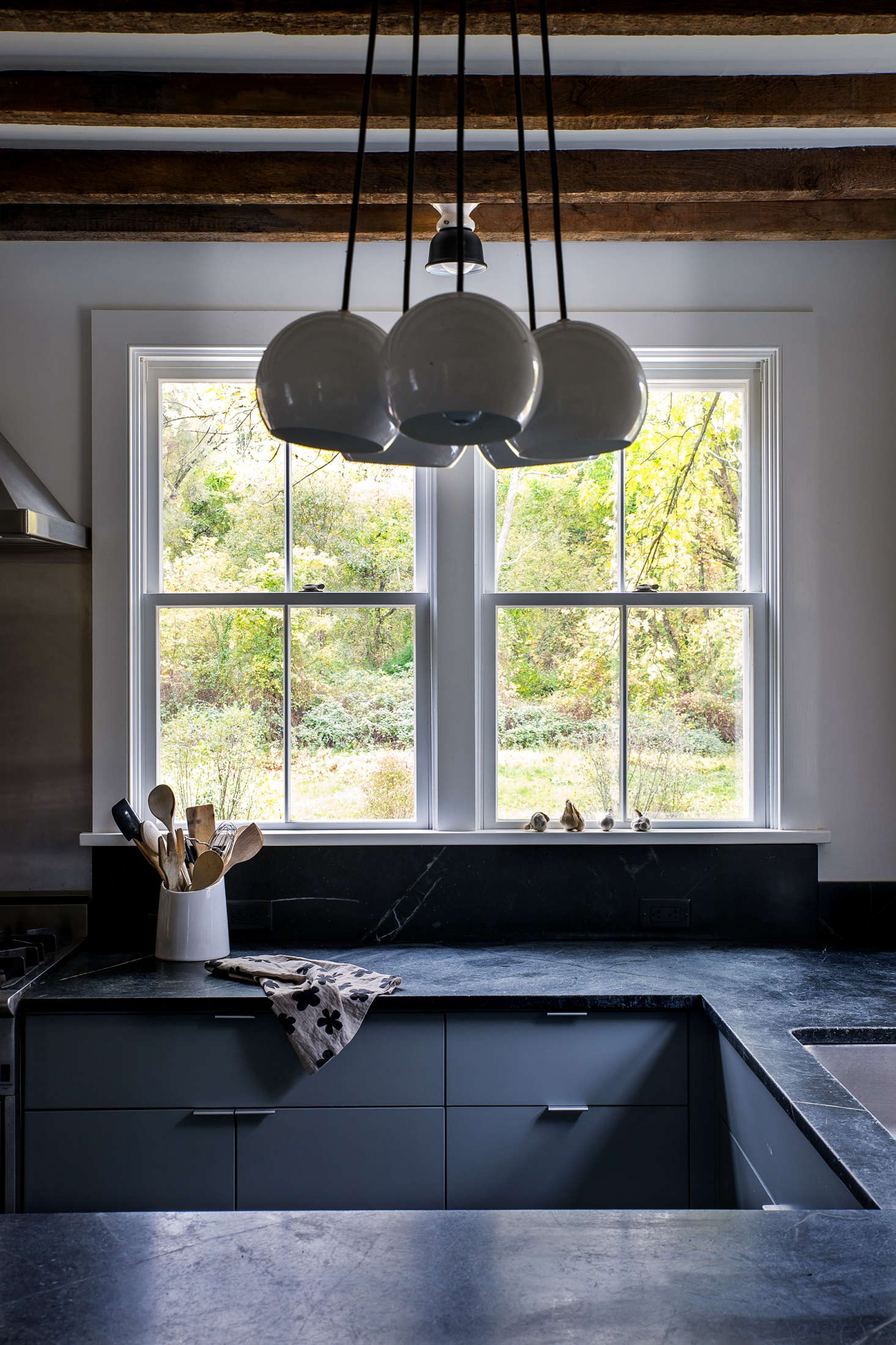 Dunja also removed a central island in favor of a U-shaped counter layout. (Thetea towel on the countertop was designed by Dunja. Visit her her online shop, Doonyaya, for similar.) A cluster chandelier from Schoolhouse Electric illuminates the breakfast bar.