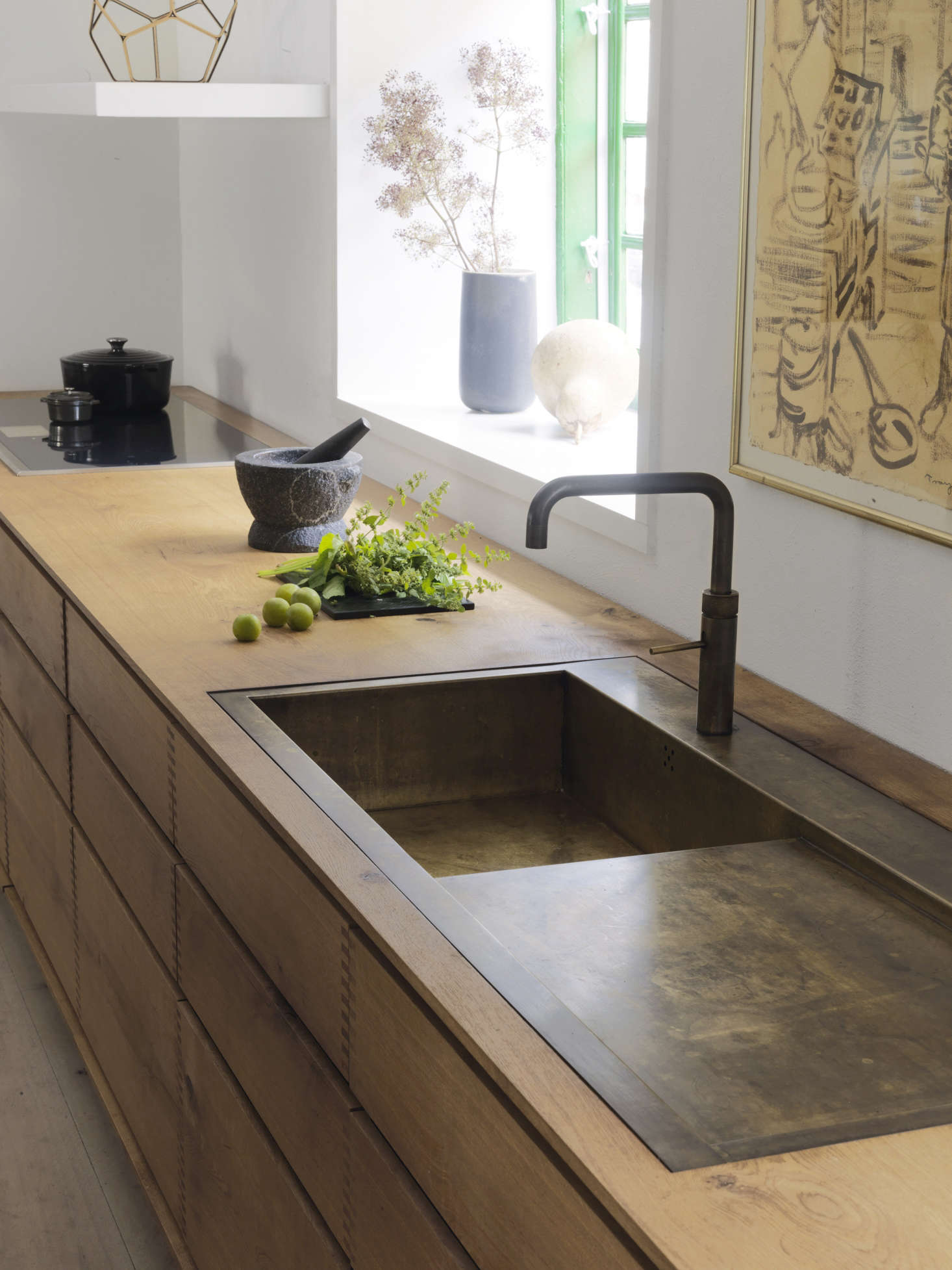 A weathered brass sink is integrated with the spacious countertop.