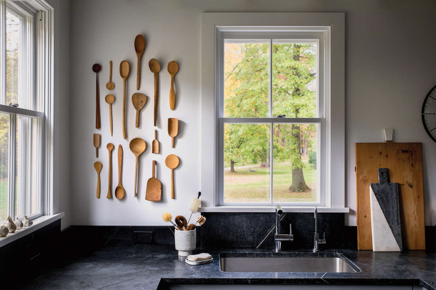 For the dramatic dark countertops, Dunja chose traditional soapstone from Barra & Trumbore in Kerhonkson, New York. Her wooden spoon installation is comprised of vintage pieces procured on Etsy and eBay. Dunja, who is a textile designer as well as a potter, made the soap dish.