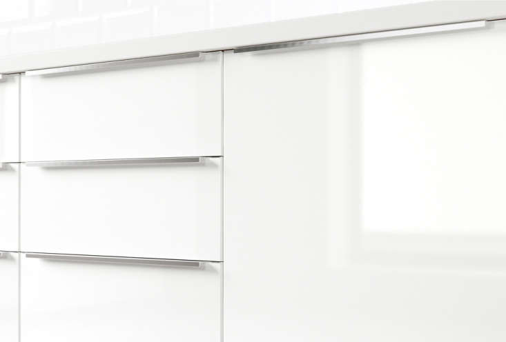 the kitchen is made up ofglossy white laminate abstrakt cabinets from ikea, a 12