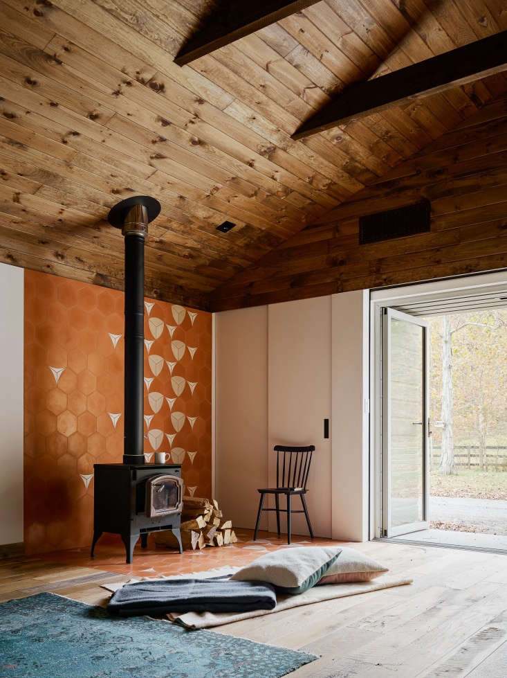 Adjacent to the sitting area is a woodstove with a tiled back wall and floor. &#8