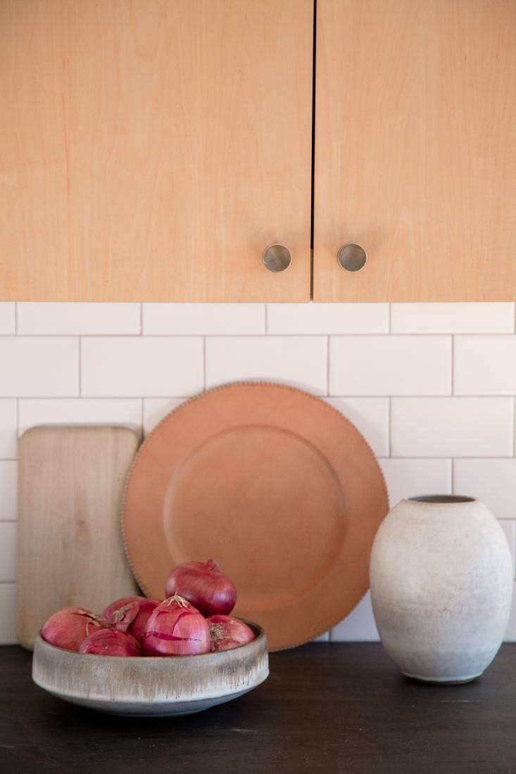The brass kitchen cabinet knobs are from Schoolhouse Electric. The Oval Vase is by Victoria Morris ($350; currently sold out online).
