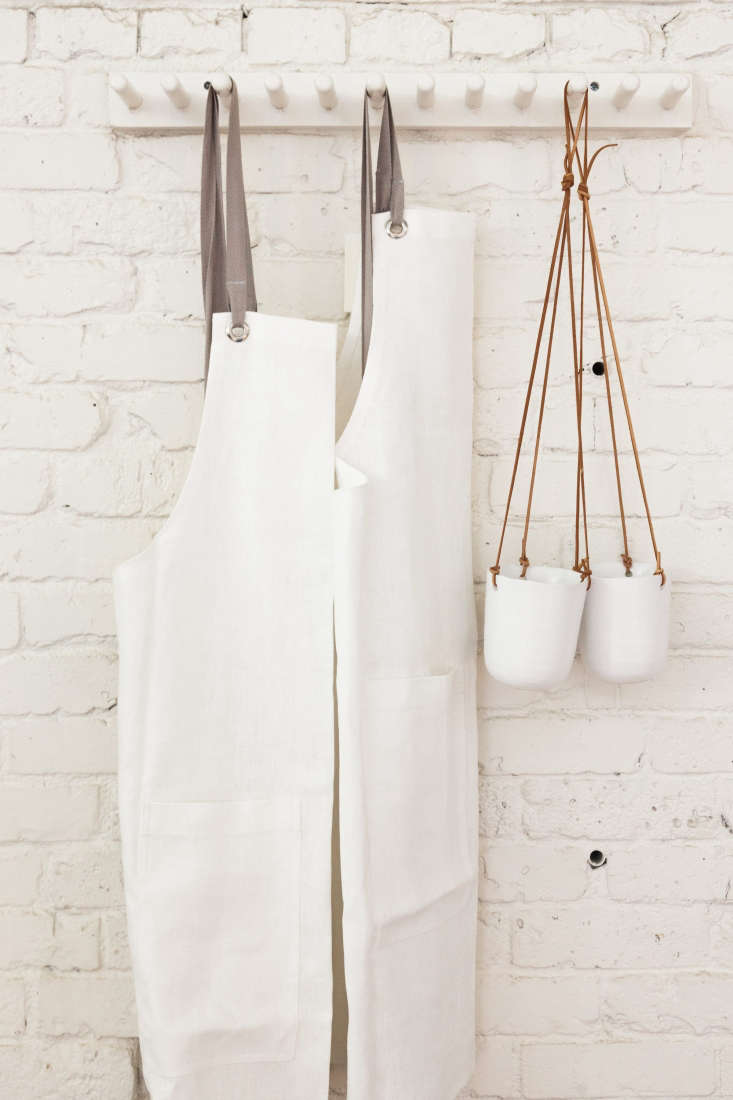 Hanging opposite the retail wall: white linen aprons by Studiopatro and a pair of hanging ceramic planters.