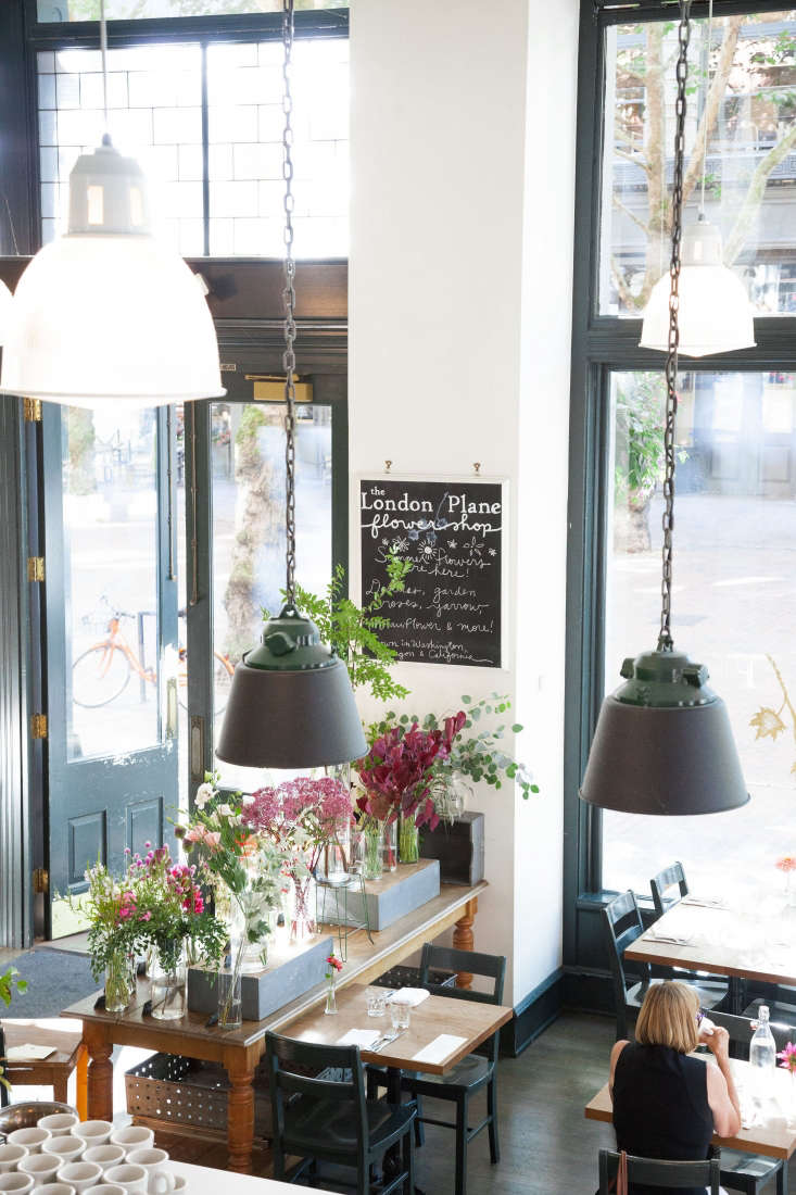 The entrance to the London Plane is flanked by a flower bar on one side and a pastry counter opposite.