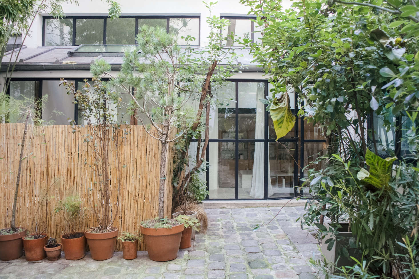 The loft, in a 90s building by commercial architects Fassio-Viaud, once functioned as a counterfeit handbag workshop. Lucile and Michel added floor-to-ceiling curtains and potted plants for privacy.
