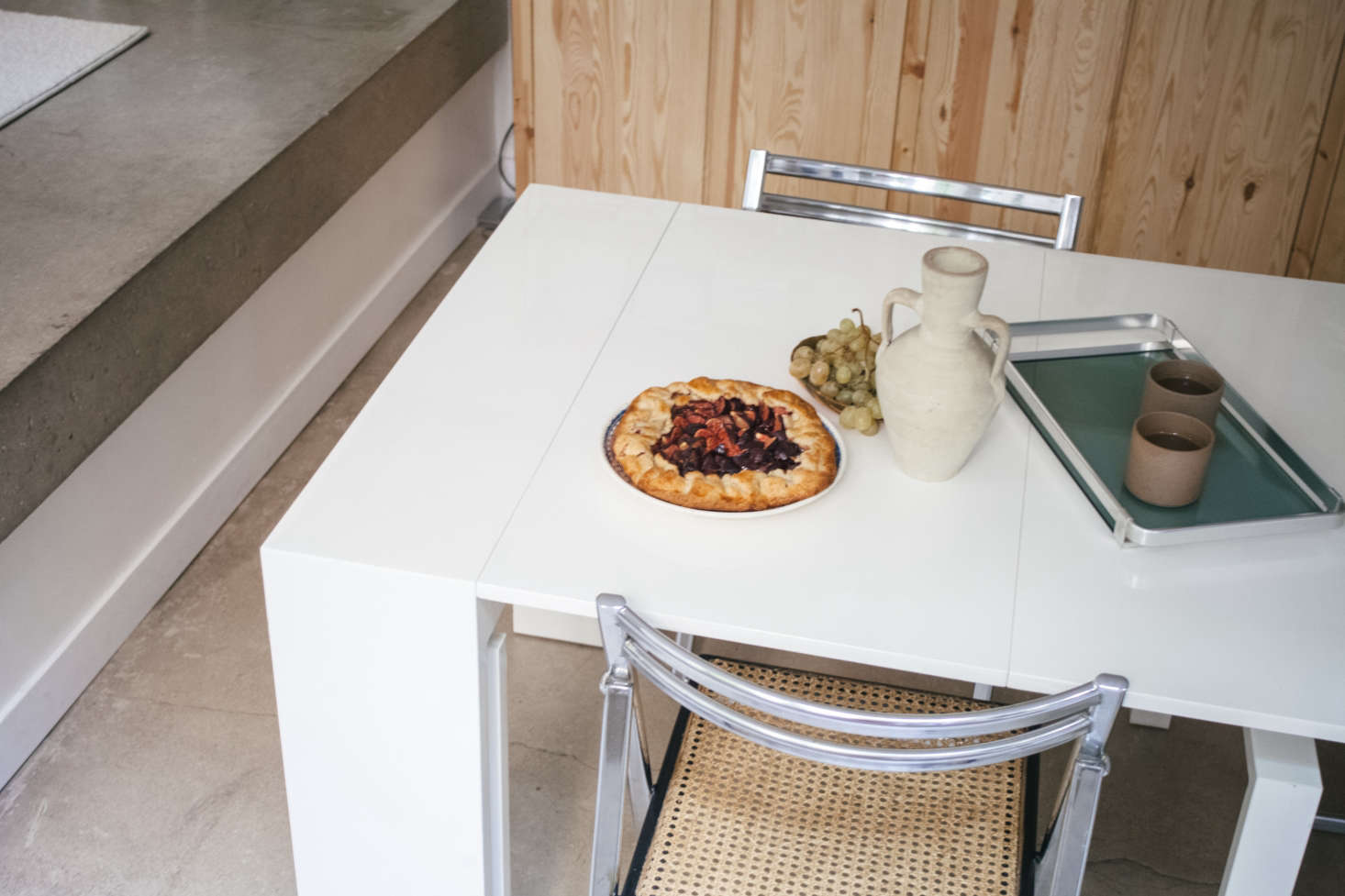 """A fig galette baked by Lucile atop a table of unknown origin that """"folds into a mini console."""" The silver tray was Michel's, and Lucile's sister Clarisse bought the chairs from a Belgian antiques website."""