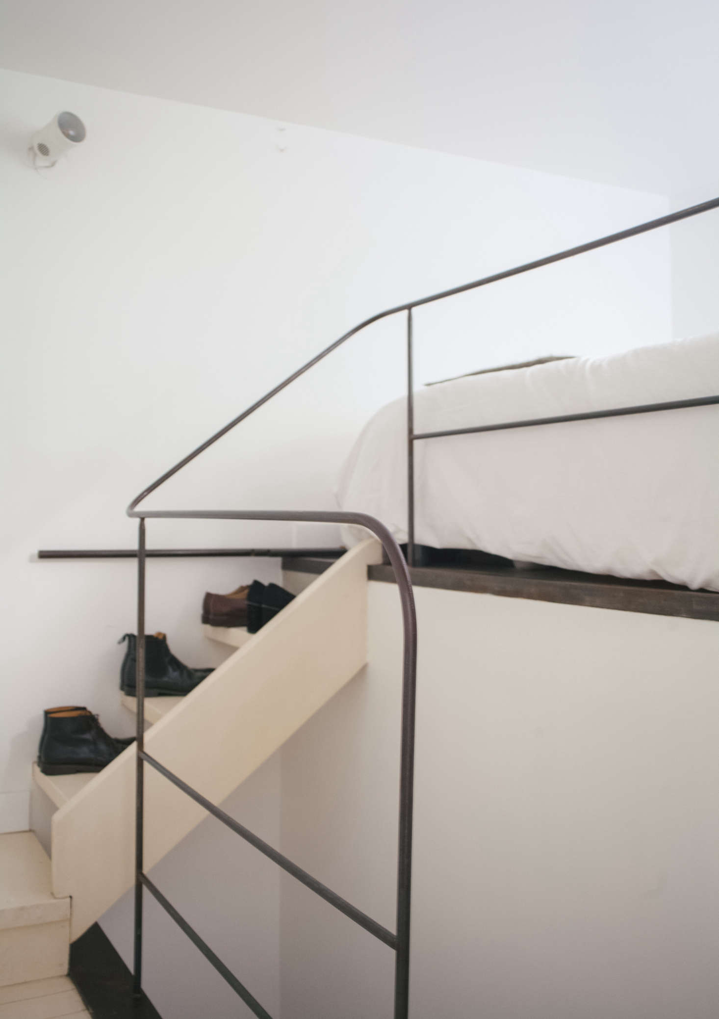 A steel handrail is one of the many timeless architectural details added by Fassio-Viaud. Lucile and Michel use one edge of the stairs to store their shoes.