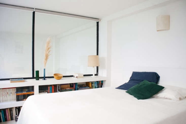 Low, built-in shelves line the Paris bedroom of French style-maker Lucile Demory. Photograph byClaire Cottrellfor Remodelista. SeeModern Thrift: Lucile Demory's Architect-Designed Rental in Paris for a look at the full apartment.