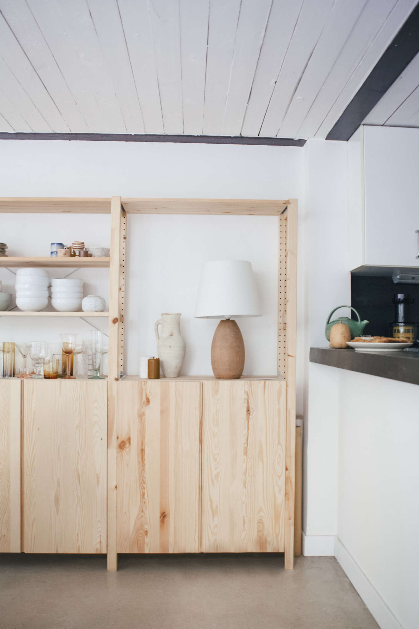 """Two side-by-side pine Ivar Shelving Units from Ikea hold Lucile's things, from """"years of collecting"""": glassware from Emmaüs, France's chain of charity shops, and Philly AIDS Thrift; ceramics by Lucile herself or by friend and artist Cécile Daladier; and a wood-base table lamp from resale site leboncoin.fr."""