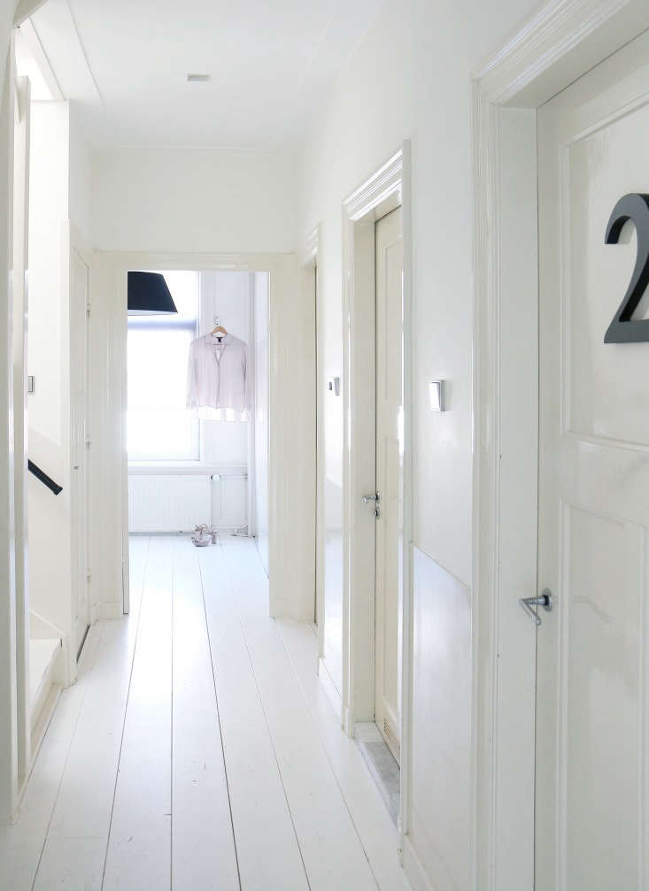 The doors have numbers in the otherwise entirely white second floor hall. The room at the end is a walk-in closet.