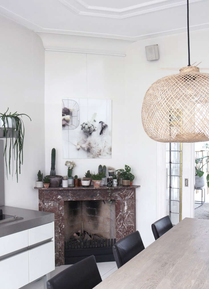 Koster masses small cactuses on the marble mantel of the kitchen fireplace, which, like its mate in the living room, is fitted with a gas burner. The woven bamboo light over the table is from Danish company Bloomingville.
