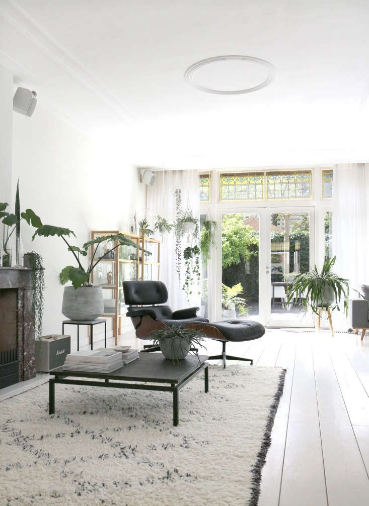 The marble mantel is original; Koster uses it to display simple greenery, such as epiphytes and cuttings in clear glass vases. Note that she keeps the surrounding wall free of art to balance the busy surroundings and instill an overall tranquility. The living room opens to a leafy terrace.