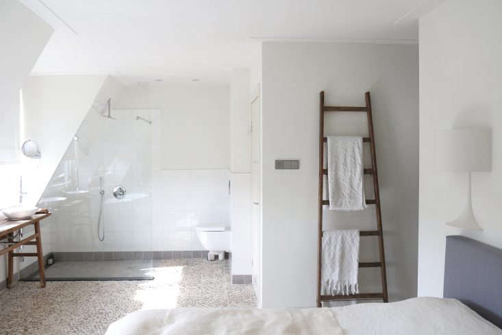 Bedroom and bath are fully incorporated. A vintage apple-picking ladder serves as a towel rack.