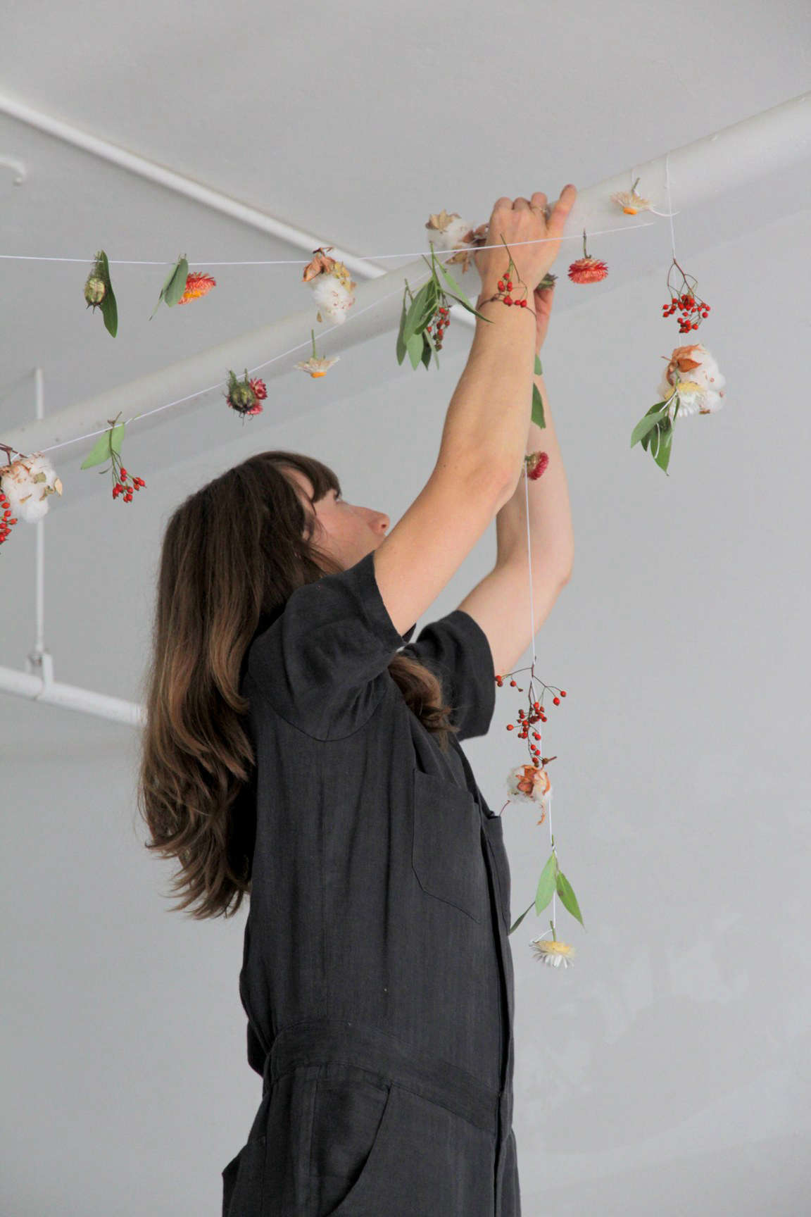 Horvath wraps the garland around exposed pipes in the restaurant.