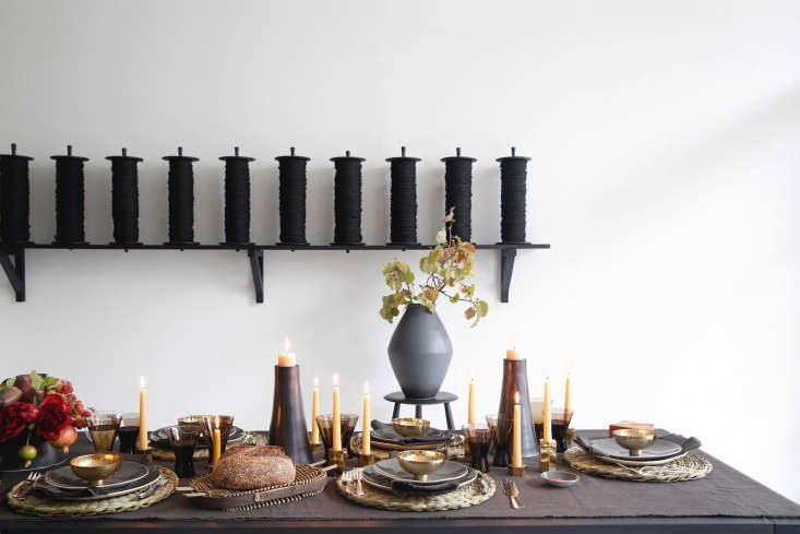 Scattered across the table is a single March Brass Menorah, which functions as nine individual candlesticks when separated; $