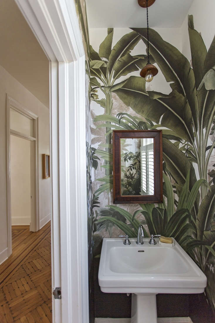 In the small bathroom, the team broke with the neutral scheme. The pendant light is by woodworker Emily Brock and the leaf-print wallpaper is by French company Ananbo.