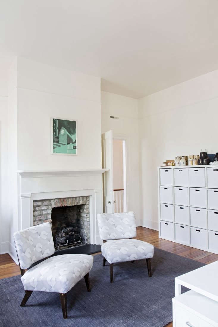 A rug and upholstered chairs, plus a working fireplace, add an at-home feel to an upstairs room. The fire is lit frequently in winter, Rowson says.