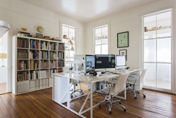 An upstairs office shares interior windows with the sun porch, which the team rents to an artist. As a result, the artist&#8