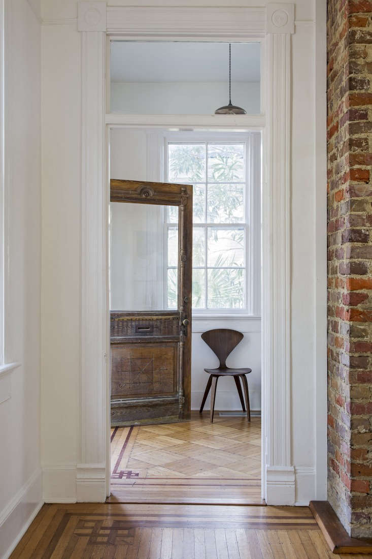 In the entryway the original, 0-year-old carved wood door mixes with a chair by Bauhaus-educated designerNorman Chernerand a commissioned pendant light by third-generation woodworker Emily Brock of Board & Bread in Nashville. Mix-and-match wood pieces throughout add a naturalistic but sculptural feel.