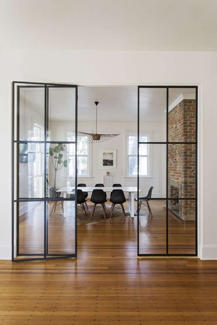 The two rooms on the first floor are separated by a custom steel-frame glass door, installed by Cole Flodin, a local metalworker, who worked with David Pastre, a professor of architecture at Clemson University, to design the structure.&#8