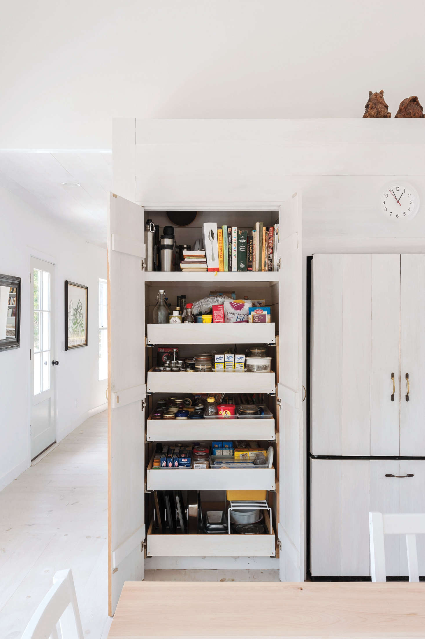 Architect Sheila Narusawa installed a wall of tall storage closets in her Orleans, Massachusetts, home. Here, the pantry stores cookbooks, dry goods, and baking tools. See more inKitchen of the Week: A Streamlined Cape Cod Classic. Photograph by Matthew Williams for Remodelista.