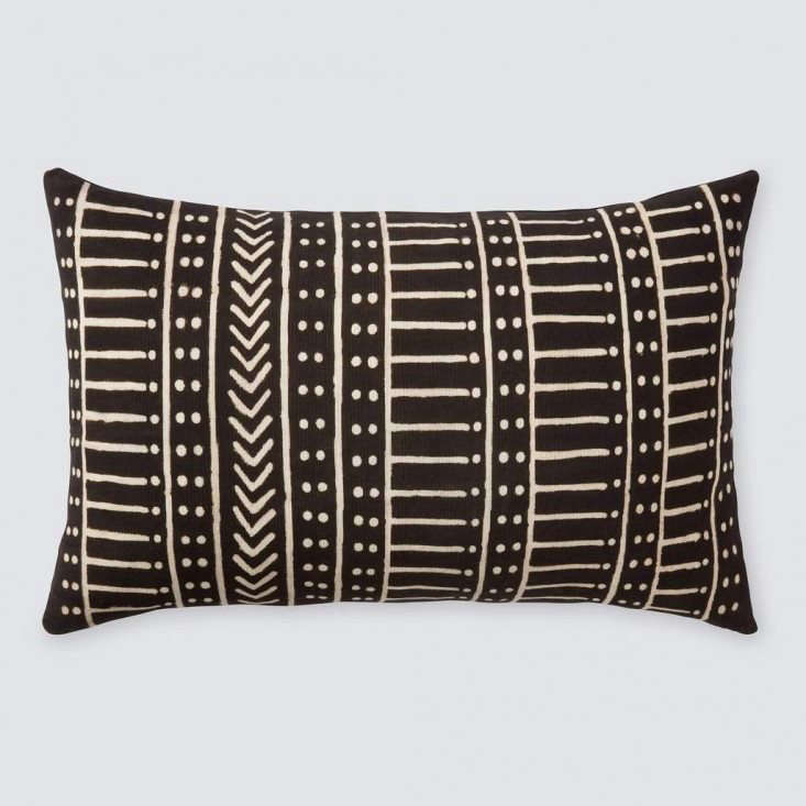 TheMinuit Mud Cloth Lumbar Pillow sports a hand-painted pattern of arrows, dots, and dashes with solid black on reverse. It&#8