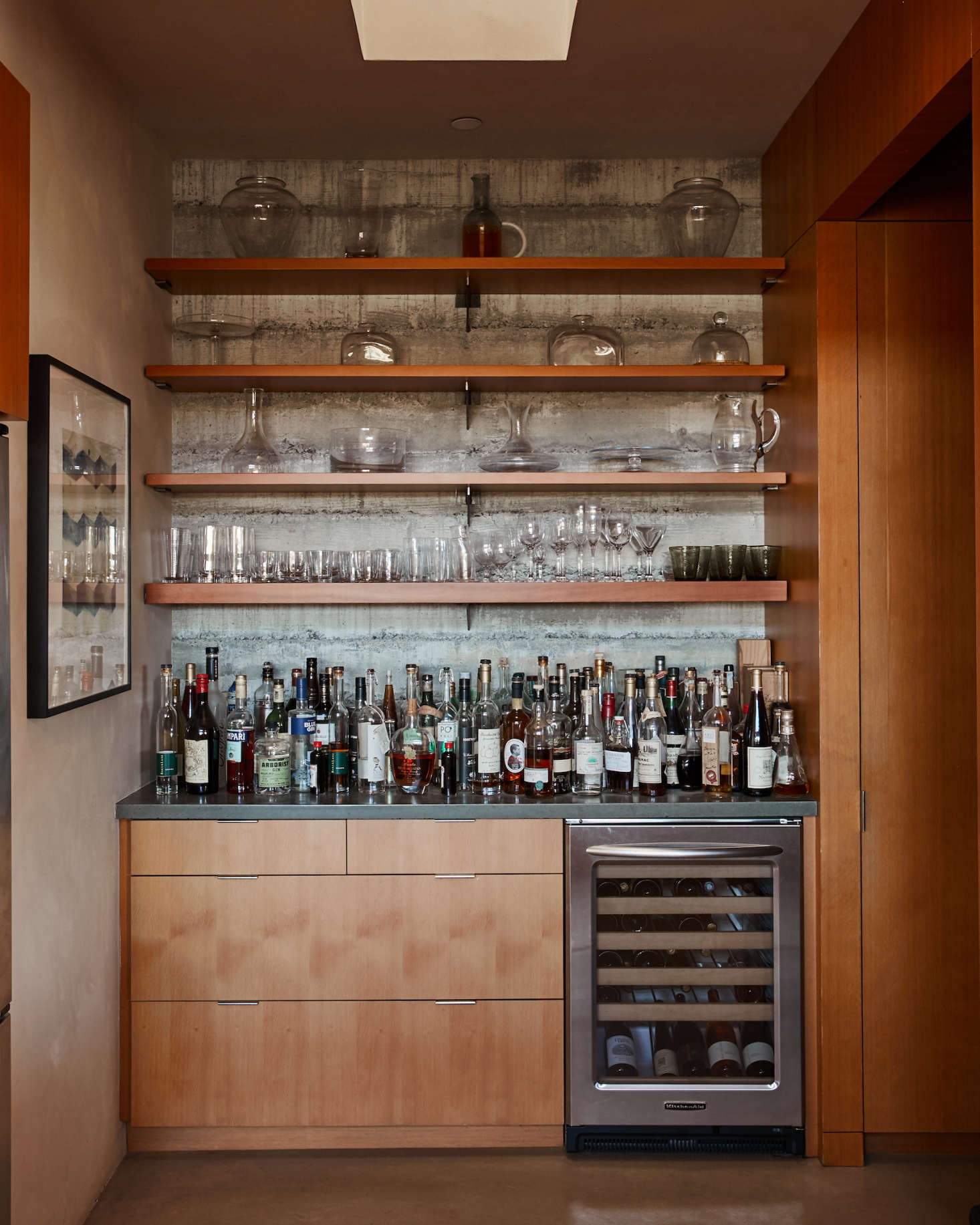 An amply stocked liquor cabinet and under-counter fridge (filled with Baker Lane wines) marks the entrance to the walk-in pantry. Floors throughout the house are concrete with an integrated pigment.
