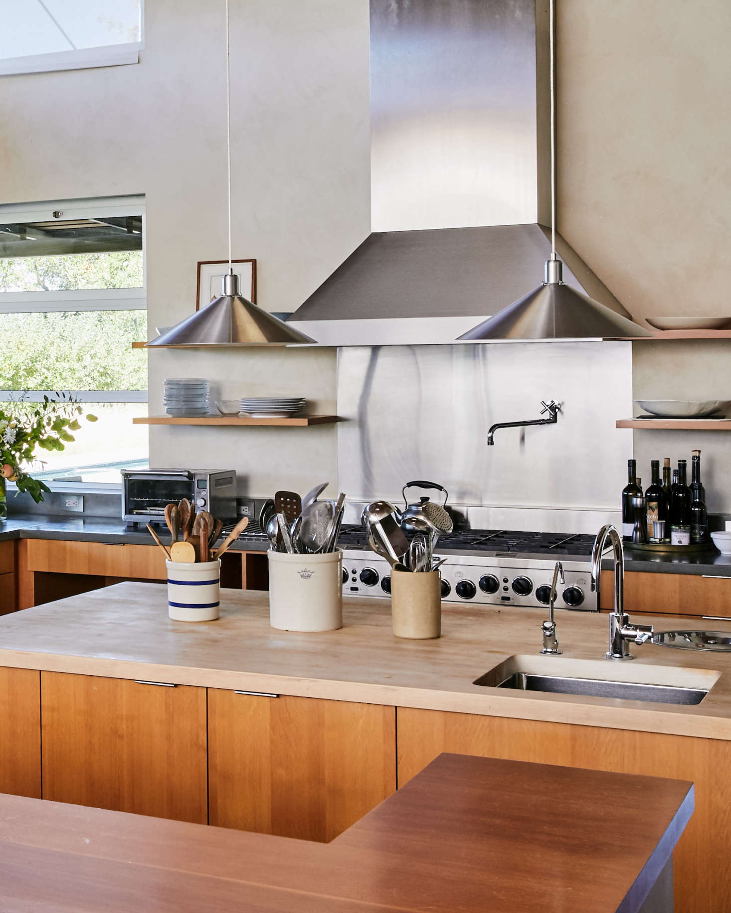 Cooking utensils are stored in stoneware crocks on the island. The custom wood cabinetry is made of vertical-grain Douglas fir, and the kitchen faucets are Dornbracht.