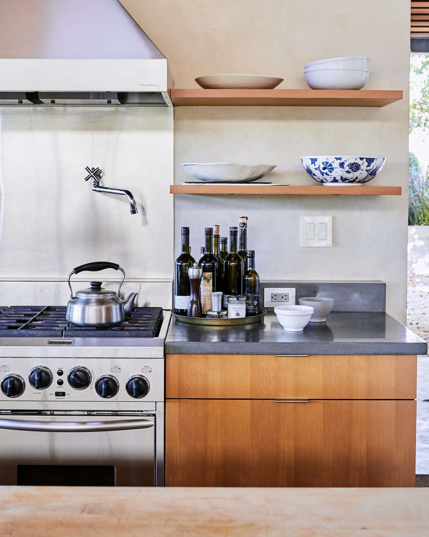 """The surrounding kitchen countertops are dark gray concrete. Within easy reach for cooking: Baker Lane Estate Tuscan Olive Oil ($)and Aceto Vivo vinegar ($). Of Baker Lane olive oils, the winemaker says, """"We don't make a lot, but it's really good.&#8"""