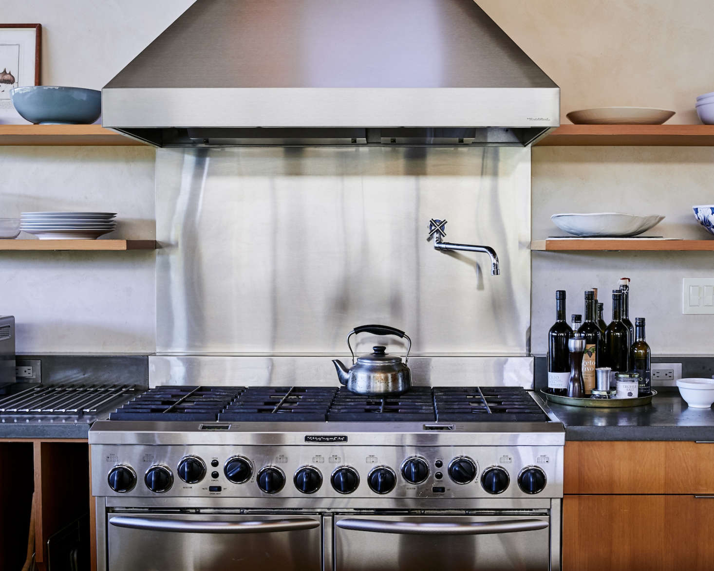 The backsplash of the oversize gas range is stainless steel, as are all the appliances (the material was chosen for its durability, said architect Anding). A Sori Yanagi Tea Kettle is perched on the stove (it&#8
