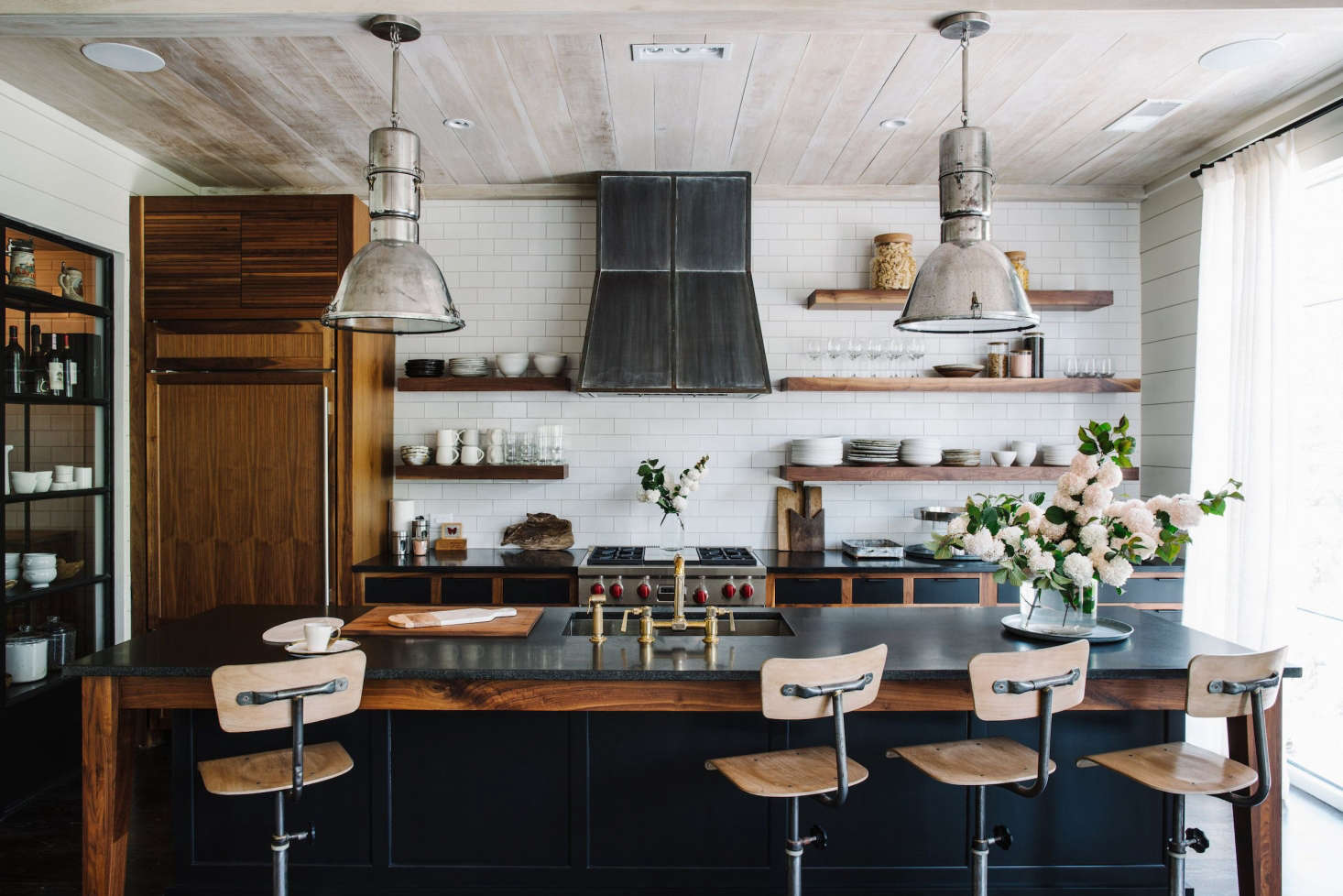 Two restored, vintage factory lights hang above the central island. The island stools are repurposed vintage schoolhouse chairs.